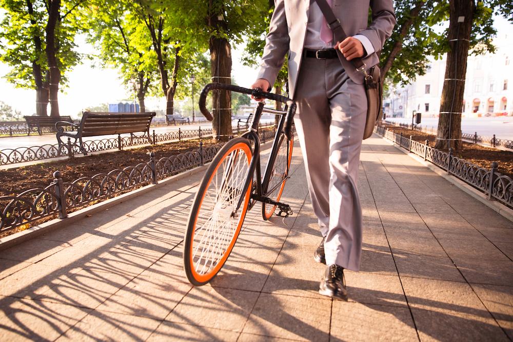 businessman-walking-with-bicycle-PQWD2UZ