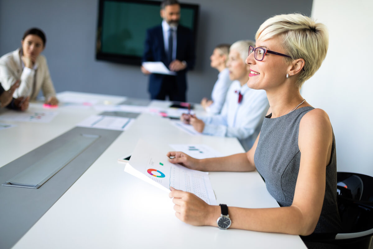 female-boss-stands-leaning-on-table-at-business-PD3WHMP