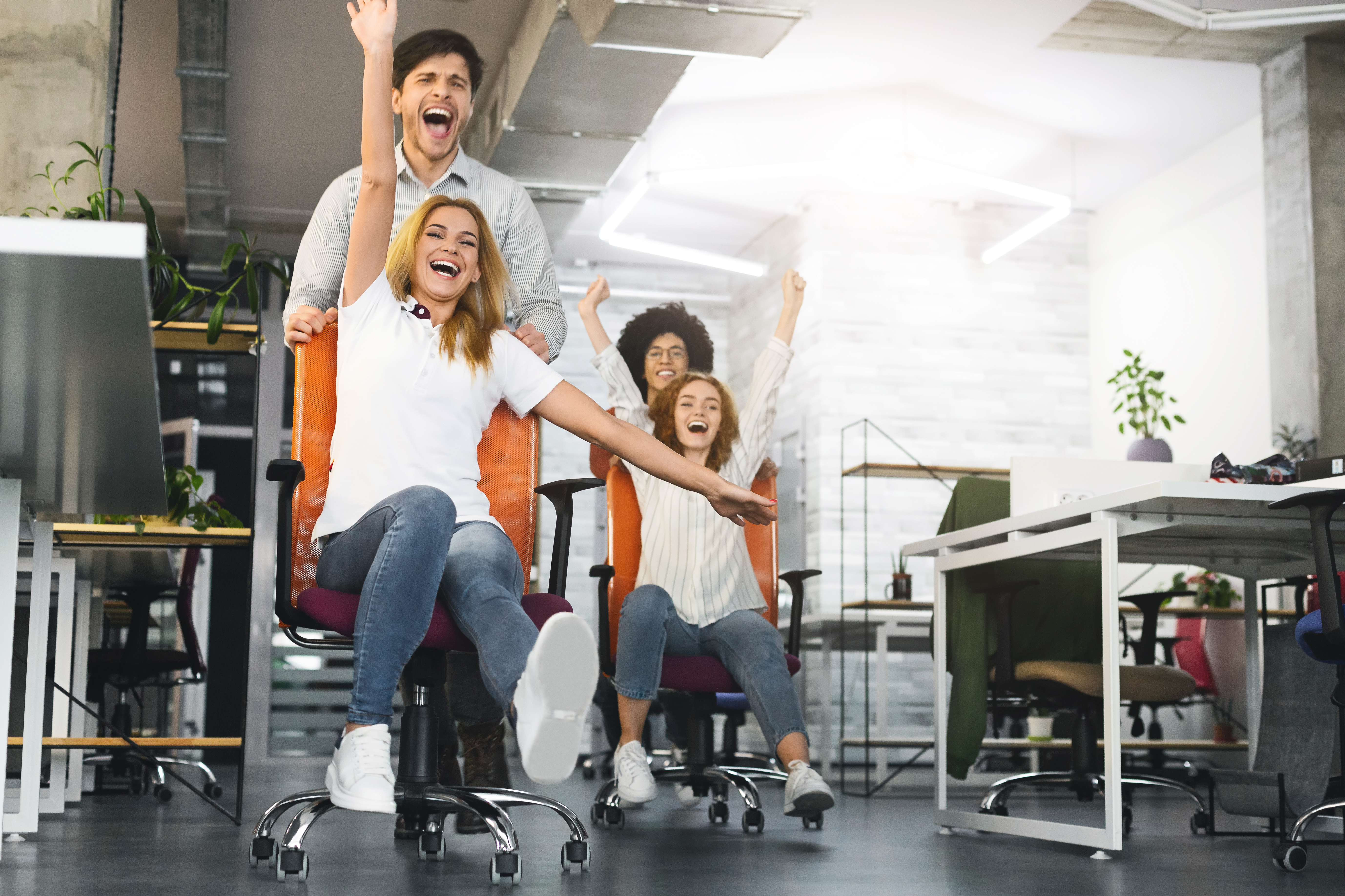 overjoyed-millennial-colleagues-racing-on-office-XBNSKL6
